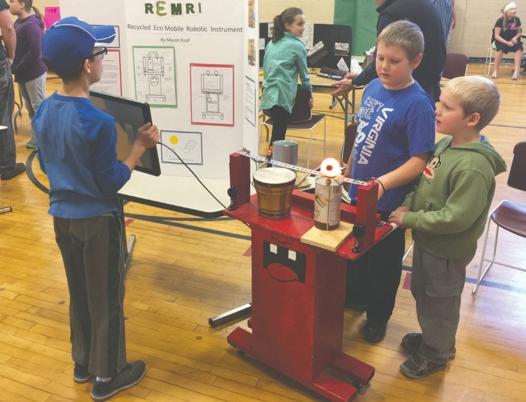 A young student shares his recycled eco mobile robotic instrument (REMRI) as part of a Green Innovators Expo. Photo by Paul Pluskwik.