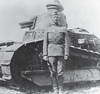 George S. Patton, who gained fame in World War II as commander of the U.S. Third Army, stands at attention in front of a military tank in 1918 in France.