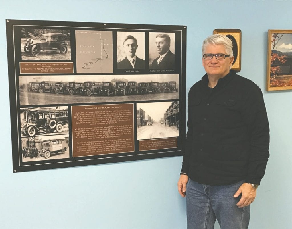 """Ron Dicklich stands near a """"Hibbing—The Birthplace of Greyhound"""" photo display at the Greyhound Bus Museum."""