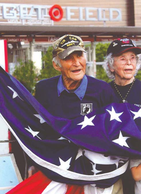 Veterans Jerry and Wendy Yourczek hold the flag at Target Field.