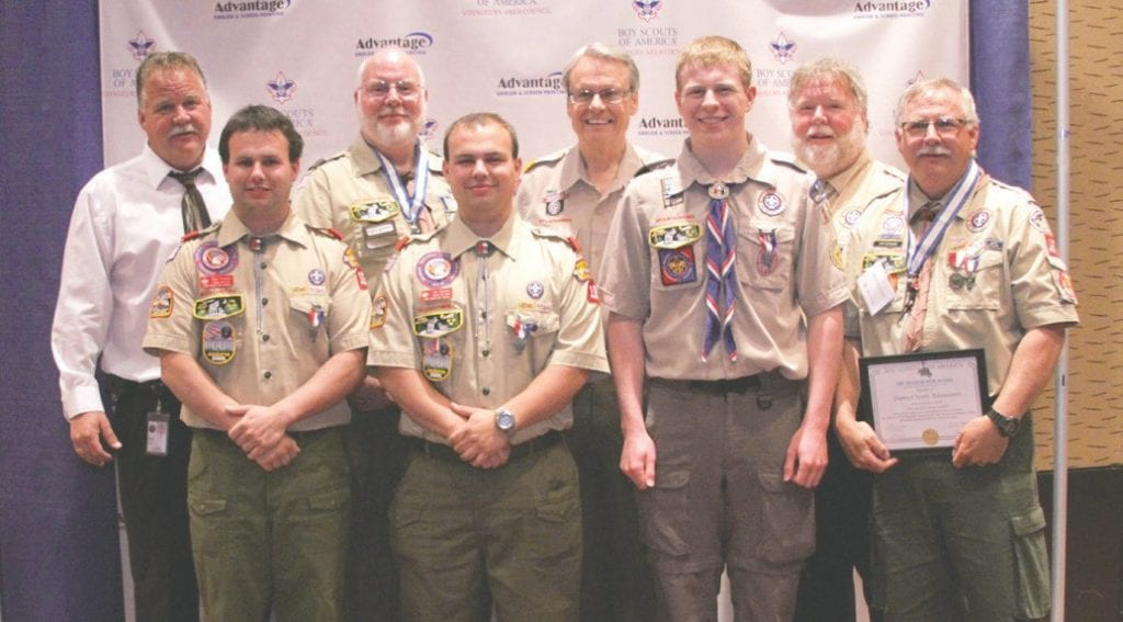 "The National Eagle Scout Association produces a magazine titled ""The Eagle's Call."" Recently Patrick Baumann, his brothers and nephews were pictured at an awards ceremony with the then-president of scouting, Wayne Brock. The photograph shows the celebration of the nine Eagle Scouts in the Baumann family. Pictured (l. to r.) front row: Zachary Baumann, Jonathan Baumann, Joshua Baumann and Daniel Baumann. Back row: Kelly Baumann, Patrick Baumann, Wayne Brock (BSA national president) and Mike Baumann. Not pictured: Roger Baumann and Mathew Leutinger. Submitted photos."