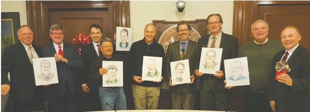The St. Louis County Board held its final meeting of 2016 and the last meeting ever for commissioners Steve Raukar and Chris Dahlberg. Commissioners are holding caricatures of themselves that had been drawn for them by now-retired Deputy St. Louis County Administrator Gary Eckenberg. Pictured (l. to r.) are County Attorney Mark Rubin, County Administrator Kevin Gray, and county commissioners Patrick Boyle, Tom Rukavina, Pete Stauber, Frank Jewell, Steve Raukar, Keith Nelson and Chris Dahlberg.