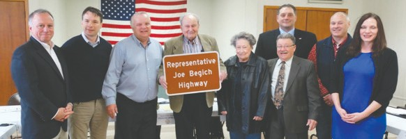 """Former State Representative Joe Begich and his wife Carol were presented with a sample of the signs that will identify CSAH 101 as Representative Joe Begich Highway in April 2017. They are surrounded by (l. to r.) County Attorney Mark Rubin, and commissioners Patrick Boyle, Keith Nelson, Tom Rukavina, Mike Jugovich, Pete Stauber and Beth Olson. """"Nobody deserves to have a lasting recognition like Joe Begich and the Begich family,"""" said Commissioner Tom Rukavina. """"They all contributed politically and have done so much for this region. Particularly Joe."""""""