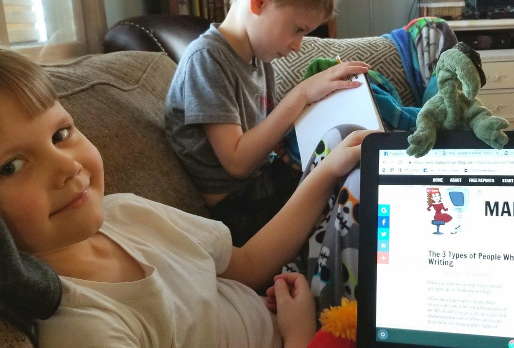 """Jennifer works from home, from the comfort of her sofa, with the help of her two sons—Jed (left) and Isaac (right)—and stuffed soft toy """"Lizzie."""" The company is great, but the assistance is somewhat lacking. Submitted photo"""