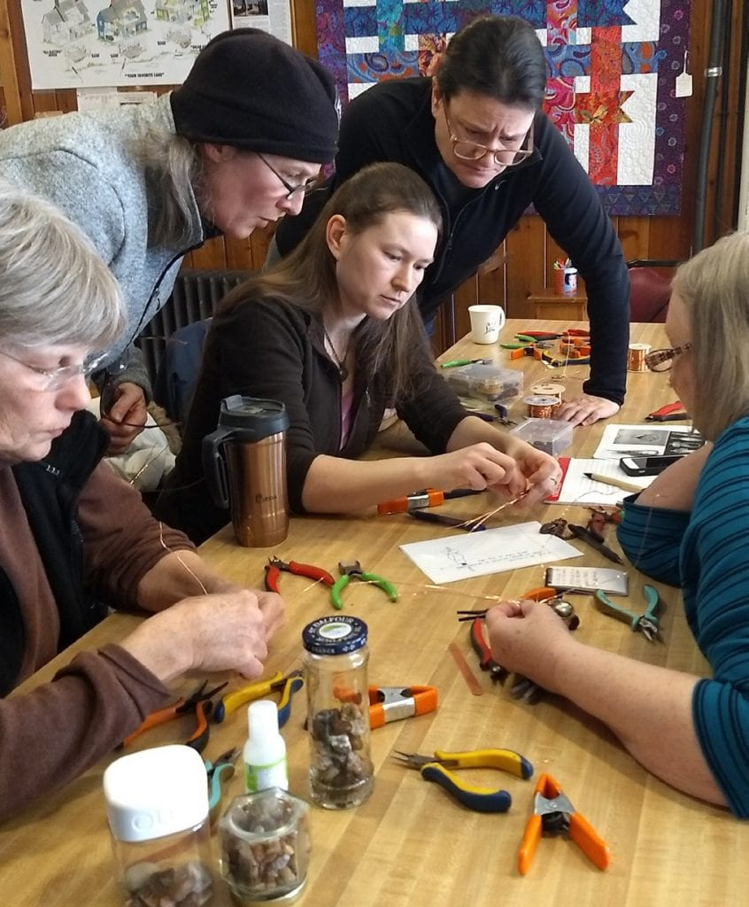 Jewelry-maker and owner of Hook and Stone Creations, Liz Engelke (center), teachers a wire jewelry class.