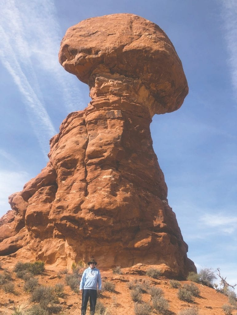 """Randy Pond is pictured in front of Balanced Rock in Arches National Park in Utah. """"Balanced Rock, one of the most iconic features in the park, stands a staggering 128 feet tall."""" —www.nps.gov"""