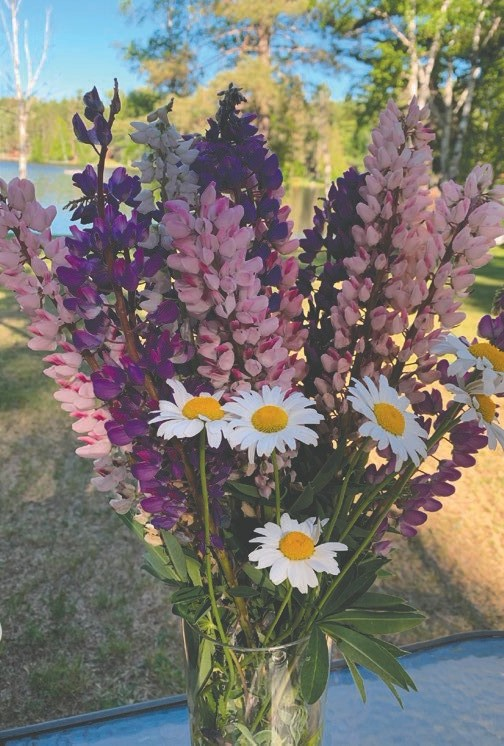 """The lakeside table for Jody's Midsummer celebration included a linen table cloth, candles, and a vase of flowers. """"I picked lupine and daisies,"""" she said. """"Both are favorites of mine."""""""
