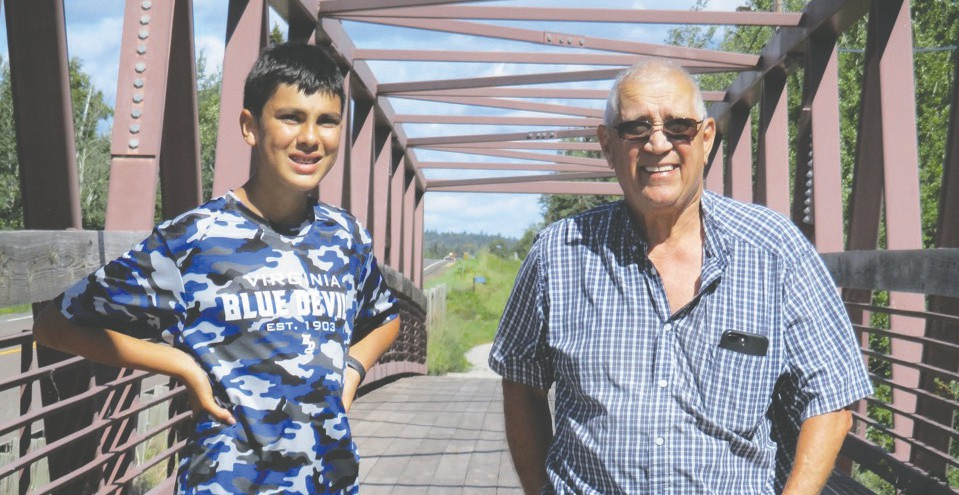 Ethan Pond and his grandfather Randy Pond pause for a photo while on a hike on Gitchi Gami State Bike Trail.