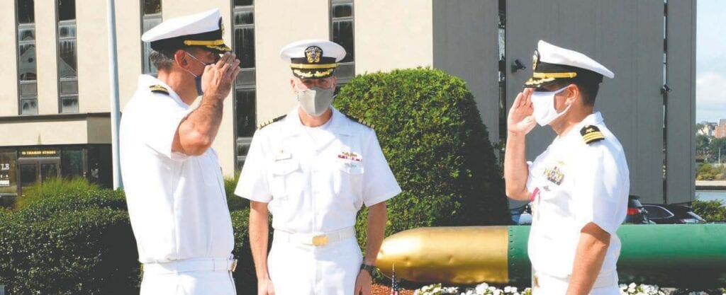 Cmdr. Brad Bozin, left, incoming commanding officer of the Virginia-class submarine USS Minnesota (SSN 783), salutes Cmdr. Thomas Flaherty, right, during a change of command ceremony at Flasher World War II Memorial in Groton, Connecticut, on September 8. Submarine Squadron (SUBRON) 4 commodore Capt. Andrew Miller, center, presided over the event. U.S. Navy photo by Chief Petty Officer Joshua Karsten.