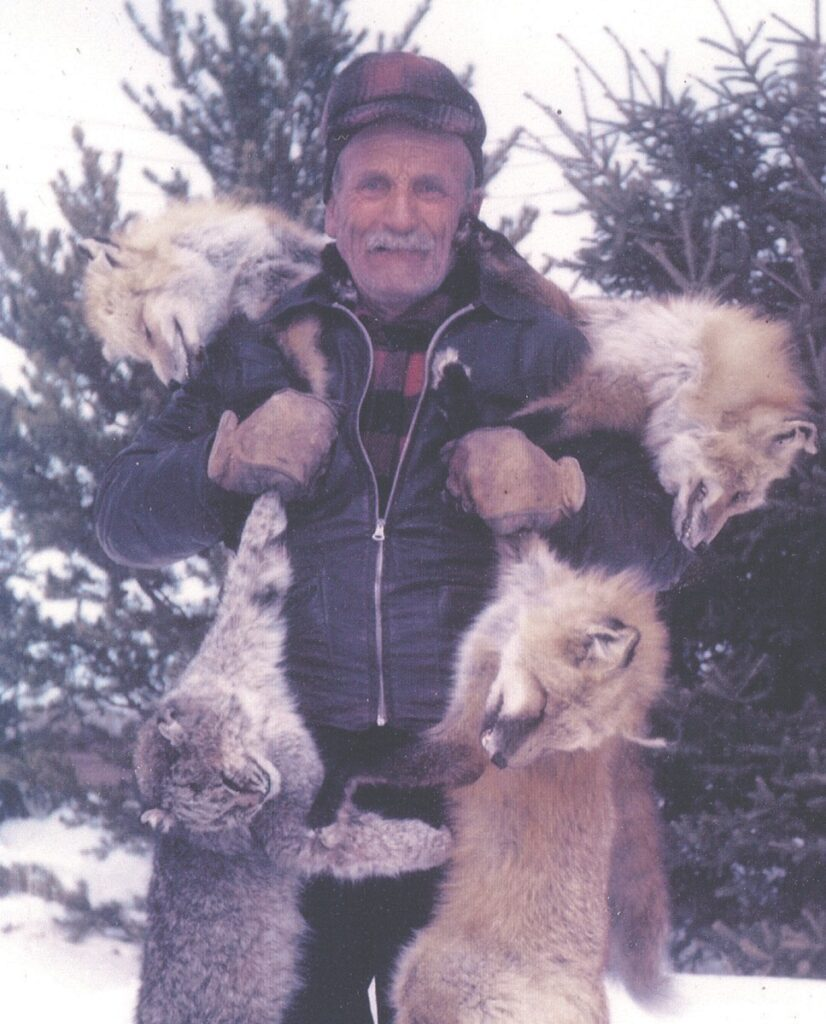 An aged Abel Pearson displays his trapping quarry. Abel began trapping and